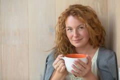 有一杯茶的中年妇女 图库摄影