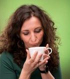 有一杯茶的卷曲妇女或咖啡 图库摄影