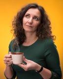有一杯茶的卷曲妇女或咖啡 免版税库存图片