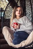 有一杯茶的女孩在一把舒适的椅子的 免版税库存图片