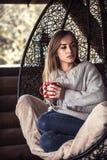 有一杯茶的女孩在一把舒适的椅子的 免版税库存照片