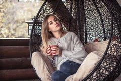有一杯茶的女孩在一把舒适的椅子的 图库摄影