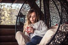 有一杯茶的女孩在一把舒适的椅子的 库存照片