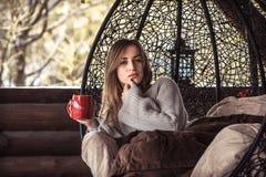 有一杯茶的女孩在一把舒适的椅子的 库存图片