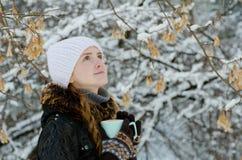 有一杯茶的女孩户外在查寻的树中 免版税库存图片