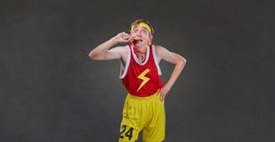 有一枚奖牌的一位滑稽的稀薄的运动员在他的手上 免版税库存图片