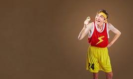 有一枚奖牌的一位滑稽的精瘦的运动员在他的手上 免版税库存图片