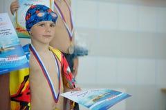 有一枚奖牌的哀伤的小男孩游泳的 免版税库存图片