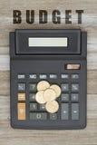 有一枚金美元硬币的计算器在被风化的木头 库存照片