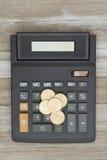 有一枚金美元硬币的计算器在被风化的木头 免版税库存图片