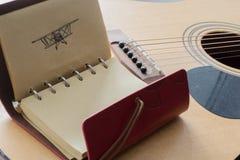 有一架飞机的笔图片的皮革笔记本在吉他的背景的 免版税库存图片
