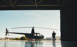 有一架直升机的飞行员在飞机飞机棚 库存图片