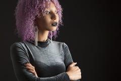 有一根五颜六色的紫色非洲的头发的黑人妇女在黑色穿戴了 库存照片