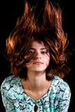 有一根吹的头发的逗人喜爱的女孩 免版税库存图片