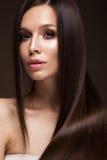 有一根完全光滑的头发的美丽的深色的女孩和经典构成 秀丽表面 免版税库存照片