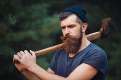 有一根巧妙的髭的残酷有胡子的人有一个轴的在他的手上在森林 库存照片