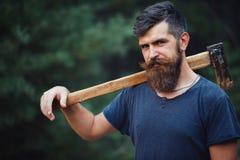 有一根巧妙的髭的残酷有胡子的人有一个轴的在他的手上在森林 免版税库存图片