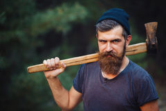 有一根巧妙的髭的残酷有胡子的人有一个轴的在他的手上在森林 图库摄影