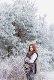 有一根柔和的甜明亮的红色头发的美丽的性感的妇女走在的冻多雪的森林 图库摄影