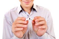有一根残破的香烟的人 库存图片