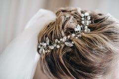 有一根珍贵的别针的美妙地被安排的头发在保留在新娘的头的面纱的头发 库存照片