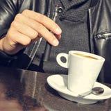 有一根电子香烟和一杯咖啡的年轻人在Th的 库存照片