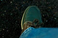 有一根皮革鞋带的绿色和破旧的鹿皮鞋 免版税图库摄影