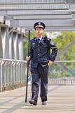 有一根警棒的警察在步行桥,北京,中国 免版税图库摄影