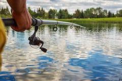 有一根钓鱼竿的一个人在河岸 库存图片