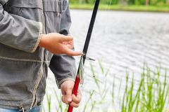 有一根钓鱼竿的人在湖附近 免版税库存照片