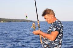 有一根钓鱼竿的人 图库摄影