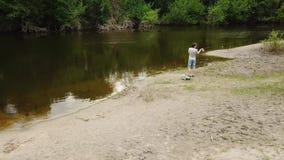 有一根钓鱼竿的渔夫在河岸 人渔夫抓一条鱼 农村逃走的概念 股票录像