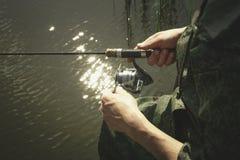 有一根钓鱼竿的渔夫在河岸 免版税库存照片