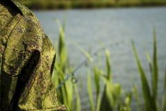 有一根钓鱼竿的渔夫在河岸 免版税库存图片