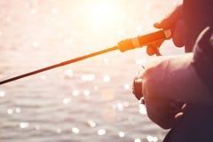 有一根钓鱼竿的渔夫在河岸 库存图片