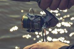 有一根钓鱼竿的渔夫在河岸 免版税图库摄影