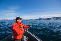 有一根钓鱼竿的渔夫运动员在他的手上 一条小船 海 免版税图库摄影