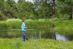 有一根钓鱼竿的男孩在河岸 库存图片