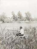 有一根钓鱼竿的老葡萄酒照片人 库存照片