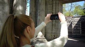 有一根长的公平的头发的少妇游人做在桦树小屋和面具门户的手机的录影 股票录像
