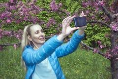 有一根长的公平的头发的年轻美丽的妇女在开花的苹果树附近拍在手机的照片 免版税库存照片