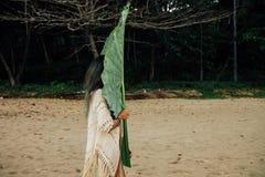 有一棵大叶子异乎寻常的棕榈树的年轻深色的妇女 图库摄影