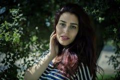 有一棵树的分支的浪漫女孩在公园 库存照片