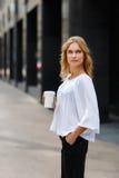 有一次性咖啡的美丽的年轻女实业家 免版税库存图片