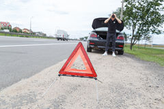 有一次故障的汽车沿着路,人设置警告三角 免版税库存照片