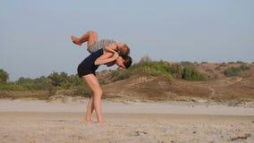 有一点女儿做的年轻运动的母亲体操在海滩 影视素材