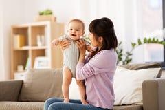 有一点婴孩的愉快的年轻亚裔母亲在家 免版税图库摄影