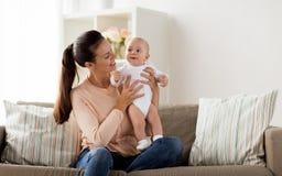 有一点男婴的愉快的母亲在家 库存照片