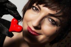 有一点红色心脏的美丽的白种人妇女在手中 免版税库存照片
