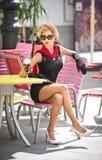 有一点黑礼服和红色围巾的时兴的可爱的夫人坐椅子在餐馆,室外射击在晴天 免版税库存图片